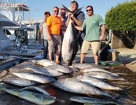 Group holding HUGE tuna caught aboard the Carly A Outer Banks fishing charter.
